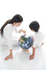 地球儀を指す母と娘