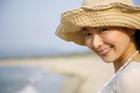 海岸で微笑む帽子の20代女性