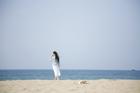 裸足で海岸を歩く20代女性