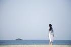 裸足で海岸に佇む20代女性