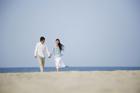 海岸で手をつないで歩く20代カップル
