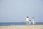 海岸を歩く30代家族3人 後姿