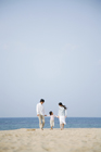 海岸を歩く30代家族3人