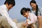砂浜で遊ぶ30代家族3人