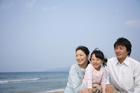 海岸で遠くを見つめる30代家族3人