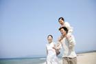 海岸で肩車をされている女の子と両親