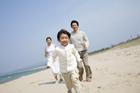 海岸を走る男の子と両親
