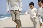 海岸を走る子供2人と父親