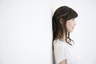 白壁にもたれ掛かる横顔の女性