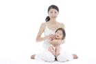 赤ちゃんを抱いて座る母親