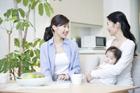 居間で乳児を抱きくつろぐ30代女性2人