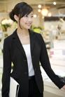 店頭で微笑む制服姿の女性