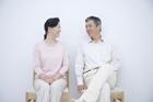 白壁の前に座り微笑むミドル夫婦