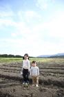 畑の中に佇む子供2人
