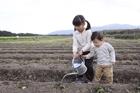 畑の土に水を撒く子供2人