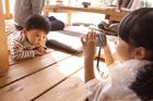 デジタルカメラで撮影する子供2人
