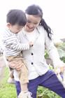 子供を抱えスコップを持つ母親
