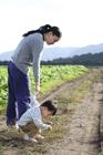 田園の畦道で石を拾う男の子と母親