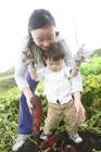サツマイモ掘りをする男の子と母親