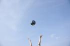 空に向かって地球儀を放り上げる手
