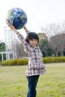 公園で地球儀を持ち上げる女の子