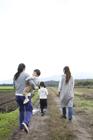 田園の畦道を歩く後姿の2組の母子