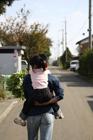女の子をおんぶして歩く父親